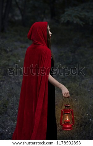 mystic girl in red cloak walking in dark forest with kerosene lamp #1178502853