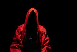 Mystic red hooded person in the darkness. Pentagram pendant on the chest. Satanic ,occult, esoteric and black magic concept. Copy space.
