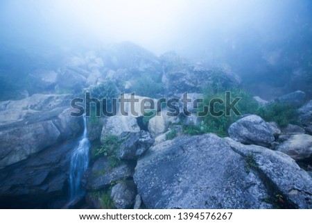 Mystic waterfall in blue misty, abstract waterfall pouring on stone rock wall in an ancient ravine. Sapa, Vietnam.