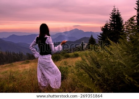 Mystic woman in ancient dress alone in a beautiful romantic sunset landscape