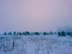 Mystical abandoned cemetery in the morning. Cemetery in winter in thick fog.