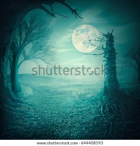 Mystical autumn forest with dead trees and roots at moody full moon night. Halloween scary background concept.