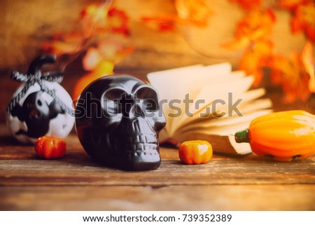 mystical background on Halloween: black book, skull and candle and pumpkins #739352389