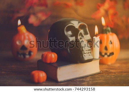 mystical background on Halloween: black book, skull and candle and pumpkins #744293158