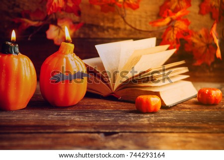 mystical background on Halloween: black book, skull and candle and pumpkins #744293164