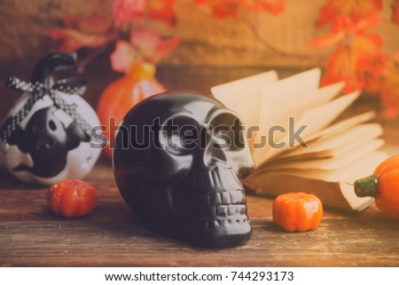 mystical background on Halloween: black book, skull and candle and pumpkins #744293173