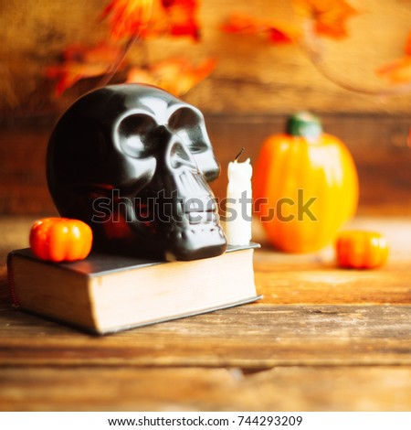 mystical background on Halloween: black book, skull and candle and pumpkins #744293209