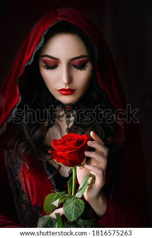 Mystical beautiful woman in a gothic costume of a medieval vampire in a hood. An adult girl holds a rose flower in her hands. Beautiful face red makeup, attractive lips. Halloween party image