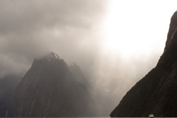 Mystical clouds and sunrays at the fjords of milfordsound in New Zealand