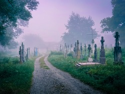 Mystical fog in an old abandoned cemetery. Foggy morning in a spooky cemetery. Stone crosses, ruins and graves.