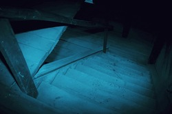 Mystical horror scary garret background to halloween. Old antique dirty wooden staircase in the dark in a mysterious paranormal spooky basement or attic with black shadow in the blue light of the moon