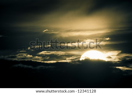 Mystical night scene. Glowing sun bathing in a dark dramatic sky