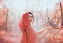 mystical pagan woman covered head peach scarf hood silk cape in autumn magic forest, holds barn owl bird. Portrait pretty face red lips. fantasy costume clothes. fog mist blossom tree spring garden
