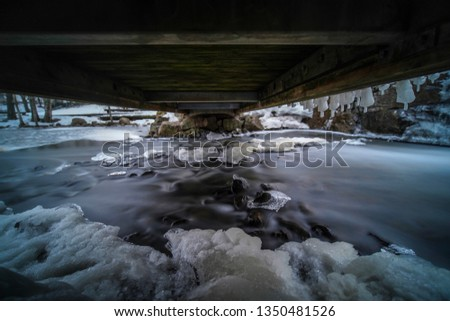 Mystical picture of small waterfall with ice on it. Shot with a fast wide angle lens and long exposure in Helsinki, Finland