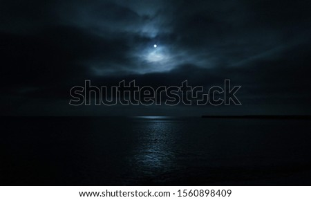 mystical picture the bright moon abive the black sea in the total darkness