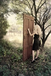 Mystical place. Girl in front of the magic door in the forest