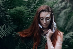 Mystical portrait with a trendy wiccan woman posing in fern leaves. Young woman with long red hair and an unusual white pattern on her skin. Close-up concept of a forest witch