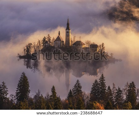 Stock Photo Mystical Sunrise over Lake in the Mountains. Mist is over the lake covering the church almost in full. Castle and surrounding Mountains are basking in the sun. Scenic and atmospheric sunrise on Bled.