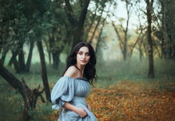mythical pretty woman Pandora, lady with tar black hair blue eyes, forest beauty in gray dress with bare shoulders hiding alone, portrait  enchantress in green grove with autumn fallen oronge leaves