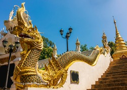 Mythical serpent sculpture with beautiful pattern along the stairway up to the Buddhist temple under blue sky