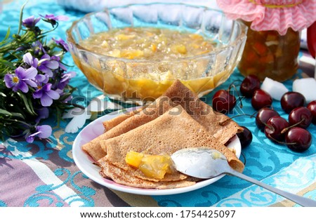 n a wooden table a vase of jam and delicious pancakes. The table is decorated with a bouquet of violets. Foto stock ©