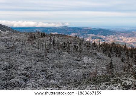 Na pierwszym planie w cieniu ośnieżone krzewy i drzewa na wzgórzu. Dale w słońcu dolina z miasteczkiem i wzgórze pokryte chmurami. Niebieskie niebo.   Zdjęcia stock ©