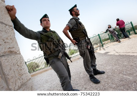 NABI SAMUEL, OCCUPIED PALESTINIAN TERRITORIES - APRIL 1: Israeli soldiers stand at their post near Palestinian young men in the West Bank town of Nabi Samuel on April 1, 2011.