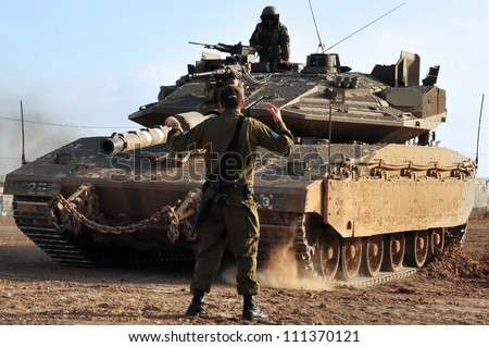 NACHAL OZ - MAY 08: Soldier directing Merkava tank on May 08 2011 in Nachal Oz, Israel .Merkava is the main battle tank used by the Israel Defense Forces.