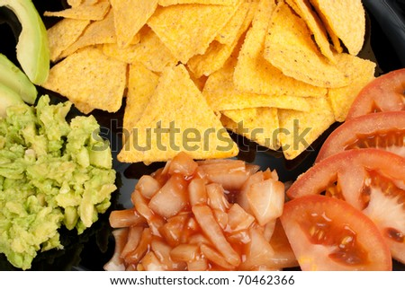 Nacho tortilla chips with dips and tomato