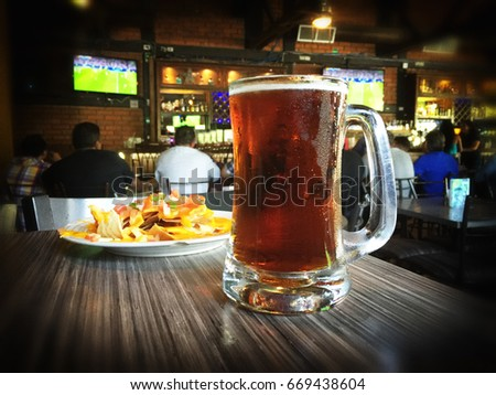 Nachos and beer on a table of a sports bar