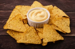Nachos and cheese dip on table