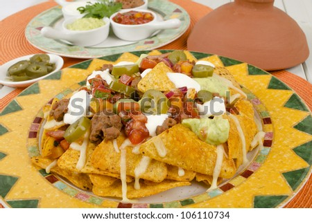 Nachos - Cheesy nachos served with sour cream, refried beans, salsa, jalapenos and guacamole on a colorful background