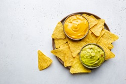 Nachos chips in a bowl with sauces guacamole and cheese, dip variety, over white stone background, top view.