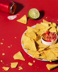 Nachos chips lie on a plate on a red background. Nearby is a spilled can of beer and lime. Sauce for an appetizer made from tomatoes. Mexican food. Beer snack. Juicy photography makes you appetite.