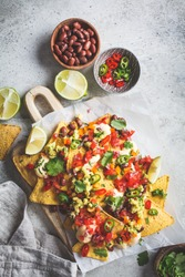 Nachos chips with cheese sauce, guacamole, salsa and vegetables on the board. Party food concept. Mexican food concept.