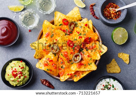 Nachos chips with melted cheese and dips variety in black bowl. Top view. Foto stock ©