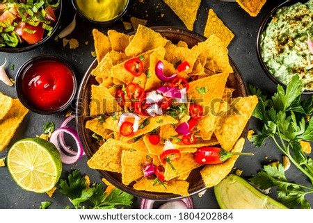 Nachos chips with melted cheese and various traditional mexican dips, salsa and jalapeno, dark grey background top view copy space Stock photo ©