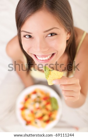 Nachos eating woman smiling looking at camera. Beautiful cute girl enjoying snacks in bed - white background.