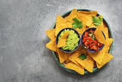 Nachos in a plate with guacamole and salsa sauce on a gray concrete background. Traditional mexican food. Top view, copy space