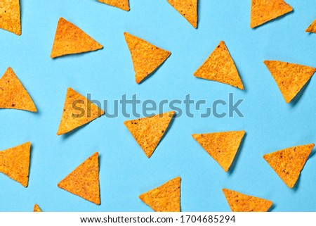 Nachos Mexican chips colorful pattern on blue background. Tortilla nacho chip closeup, fashionable trendy flat lay. Crisps nachos snack wallpaper, top view. Creative concept
