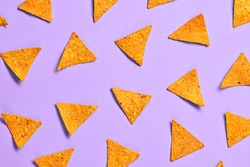 Nachos Mexican chips colorful pattern on purple background. Tortilla nacho chip closeup, fashionable trendy flat lay. Crisps nachos snack wallpaper, top view. Creative concept