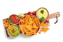 Nachos Mexican corn chips with guacamole, salsa, cheese dip sauce. Vegan healthy nachos snack isolated on white background, top view. Tortilla nacho crisps on wooden board.