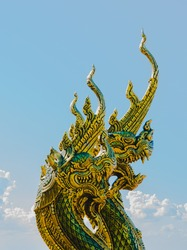 Naga head Buddhist with blue sky on background, the art of Sirindhorn Wararam temple Ubon Ratchathani Province, Thailand