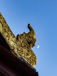Naga on the roof gable of chapel or church in Buddhist temple in Thailand with the moon in the sky that looks like being spit out from the mouth of a Naga.