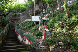 Naga Serpent stairway for thai people and foreign travelers walking up go to Tham Muang On cave in mountain for travel visit respect praying of Mae On at San Kamphaeng in Chiang Mai, Thailand