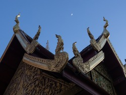 Nagas on the gable of chapel or church in Buddhist temple in Thailand with the moon in the sky.