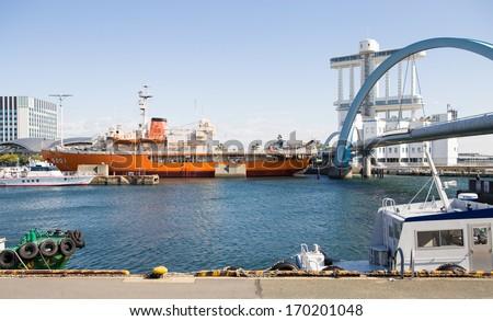Nagoya - 26 OCT : An Orange safety boat of coast guard sink at Nagoya Port and blue sea with background of Nagoya town. On OCTOBER 26, 2013 in Nagoya, Japan