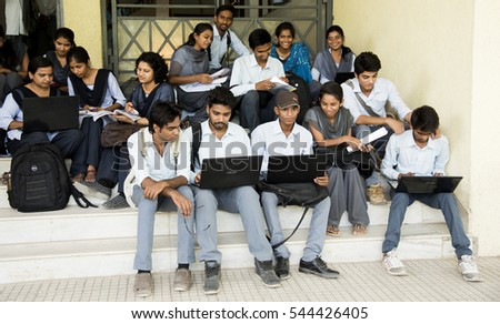 NAGPUR, MAHARASHTRA, INDIA, 11 APRIL 2016 : unidentified young university students talking together about their studies project on the outdoors staircase at university campus.  #544426405
