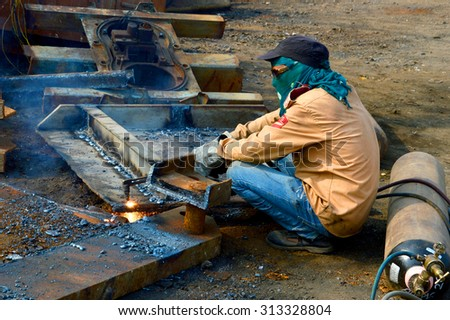 NAGPUR, MAHARASHTRA, INDIA - MAR 27: Unidentified Welders in their workshop cutting the pieces of iron for melting on Mar 27, 2014 in Nagpur, India.
