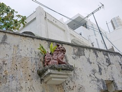 Naha city old street decoration with traditional okinawan magic guardian creature sculpture on concrete wall, Okinawa, Japan
